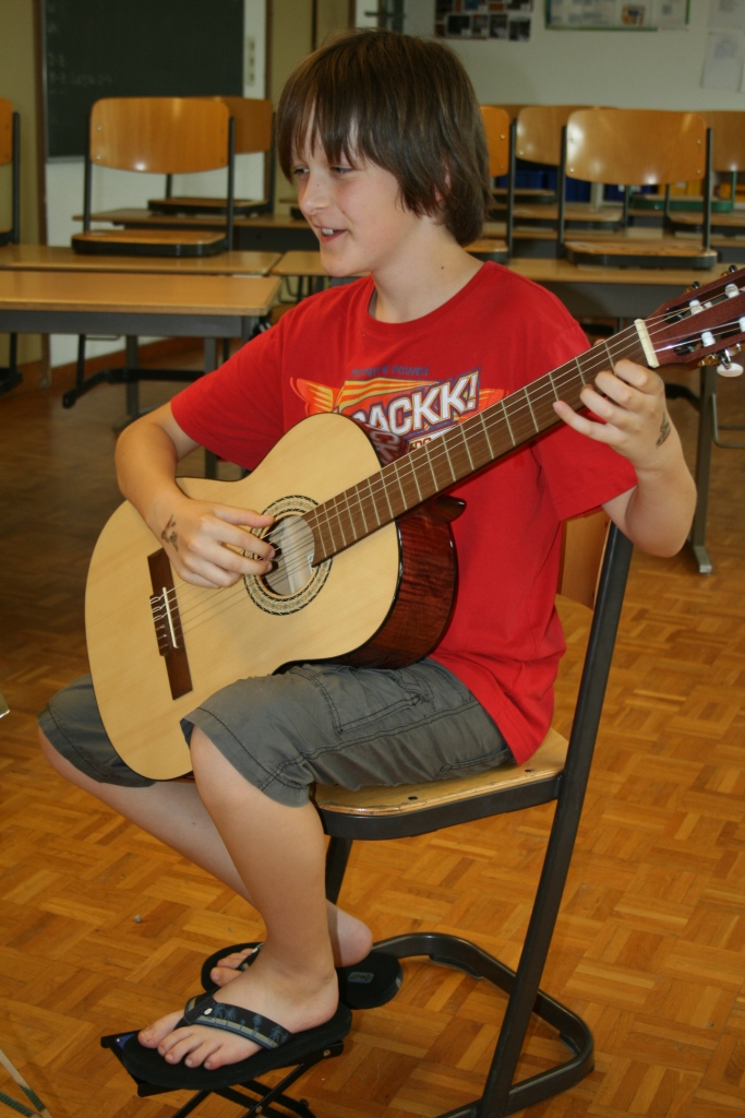 Junge im Gitarrenunterricht